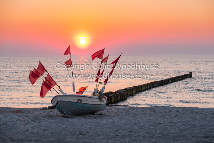 photo showing Fishing Boat On The Beach At Sunset At Ahrenshoop, Mecklenburg-Vorpommern, Germany