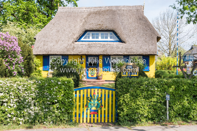 photo showing Typical Thatched Cottage And Garden At Born Auf Dem Darss, Mecklenburg-Vorpommern, Germany